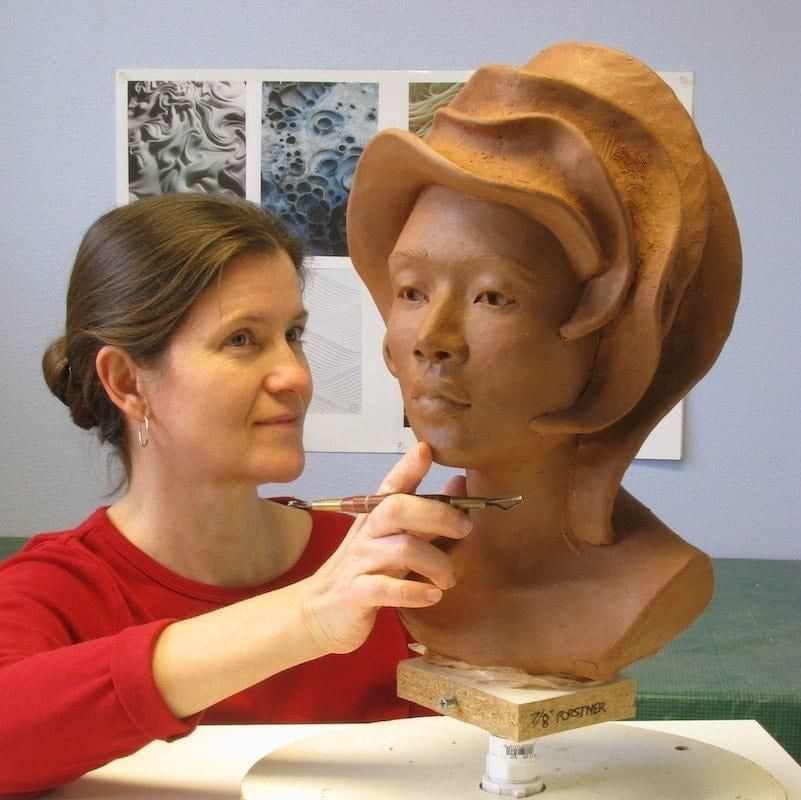 "Christine L. Evans working in the studio on the ""Luna"" bust sculpture."